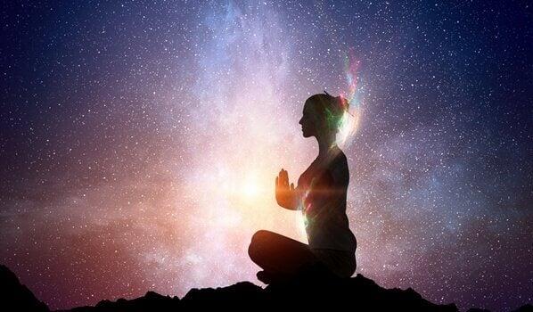 Eine Frau meditiert unter dem freien Sternenhimmel.