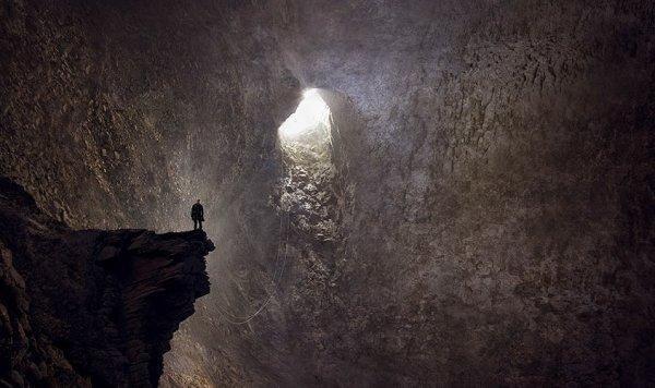 Mann in einer Höhle, der Richtung Ausgang blickt