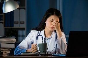 Eine Ärztin sitzt erschöpft an ihrem Schreibtisch.
