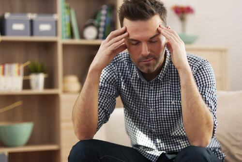 Erschöpfter Mann stützt seinen Kopf auf seinen Armen ab