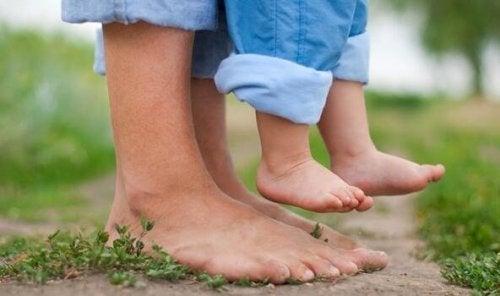 Die Füße einer Mutter und ihres kleinen Kindes, das sie hochhält.