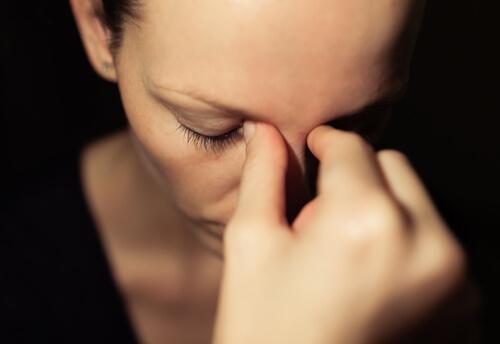 Frau langt sich gestresst an den Kopf