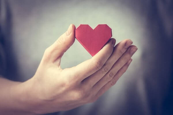 Eine Person hält ein Origami-Herz in der Hand.