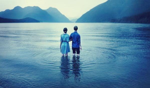 Paar steht inmitten eines Sees