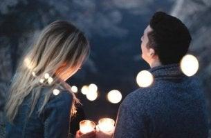 Paar hält Kerzen und genießt Magie der ersten Male