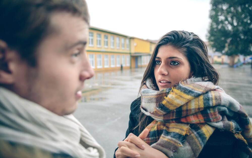 Paar unterhält sich vor einem gelben Gebäude