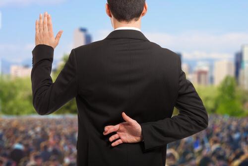 Politiker kreuzt während Eid Finger hinter dem Rücken.