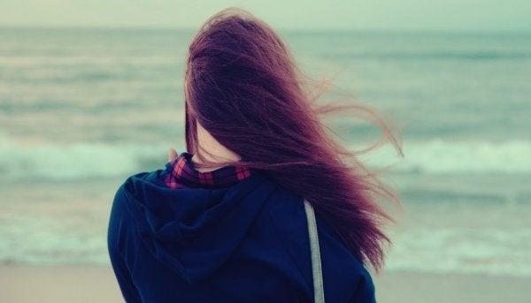 Ein Mädchen steht am Wasser.