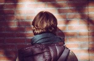 Junge steht vor einer Wand