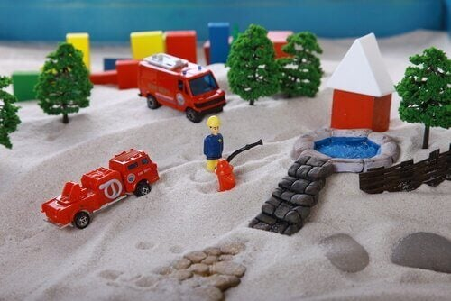 Eine Sandkiste mit Playmobil-Figuren.