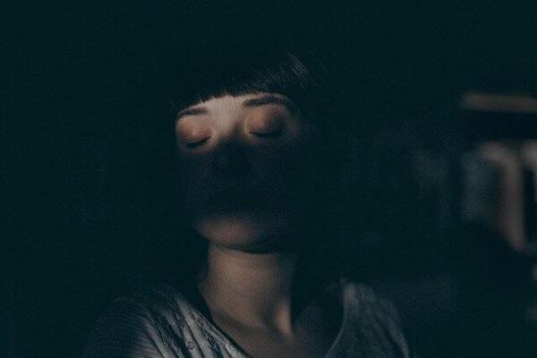 Eine junge Frau schläft in der Dunkelheit.