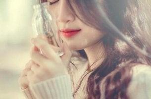 Lernen, sich selbst zu schätzen - Frau schaut eine kleine Glasflasche an
