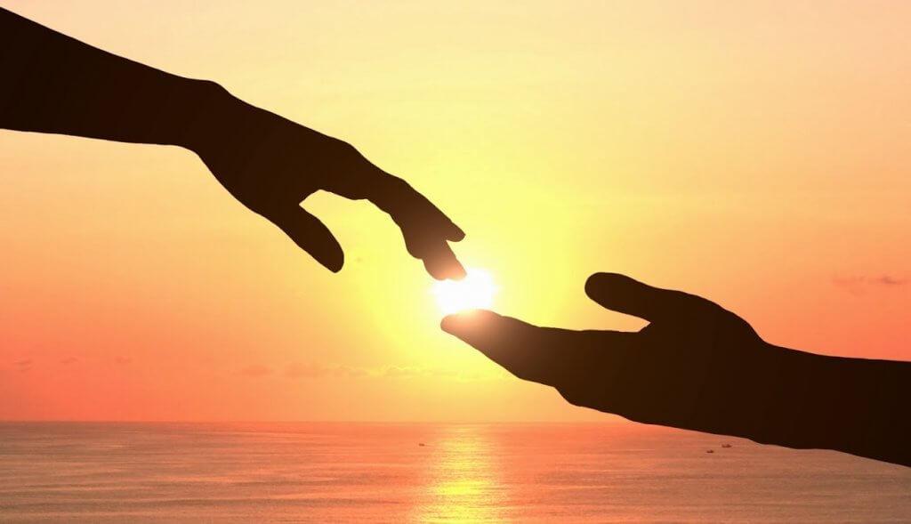Hände berühren sich bei Sonnenaufgang