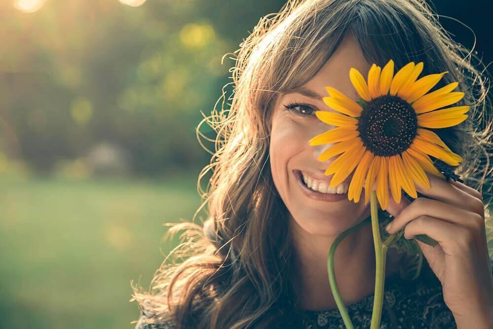 Lachende Frau hält sich eine Sonnenblume vors Gesicht