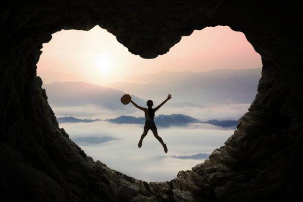 Eine Person springt in einer herzförmigen Höhle.
