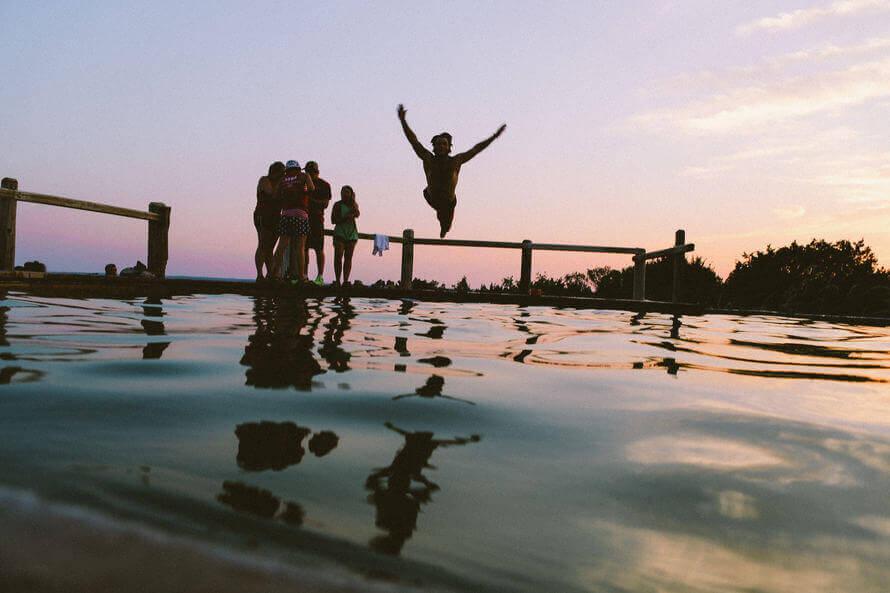 Am Abend springt ein Mann fröhlich in den Pool