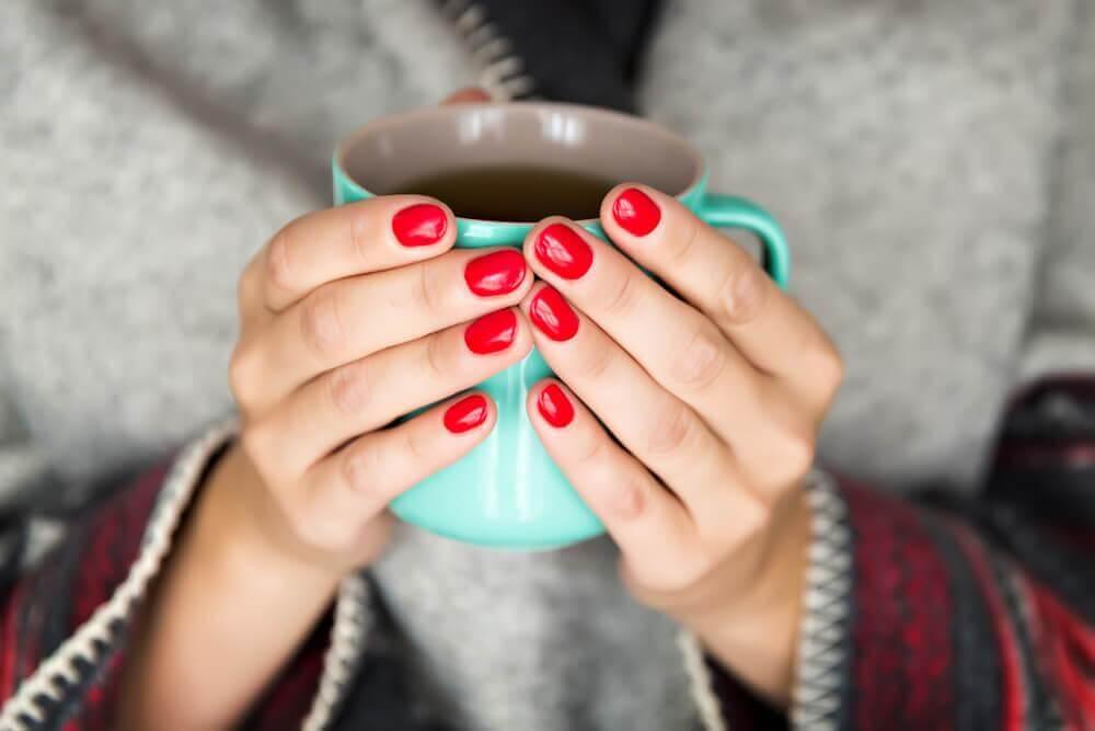 Frau mit roten Fingernägeln hält eine mintgrüne Tasse
