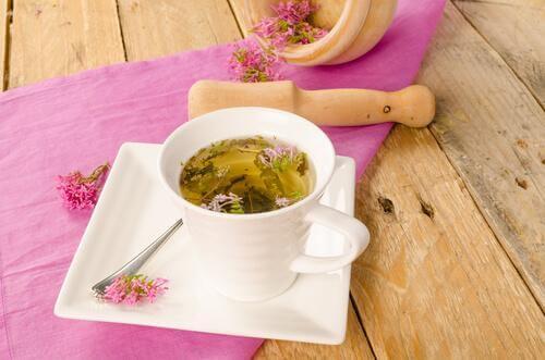 Teetasse mit Baldriantee steht auf Holztisch.