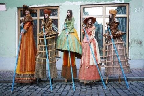 Frauen auf Stelzen in traditionellen Gewändern