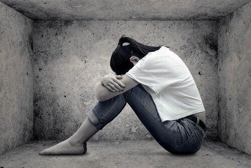 Eine traurige Frau sitzt auf dem Fussboden.