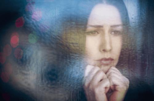 Traurige Frau schaut aus dem Fenster - Happykratie