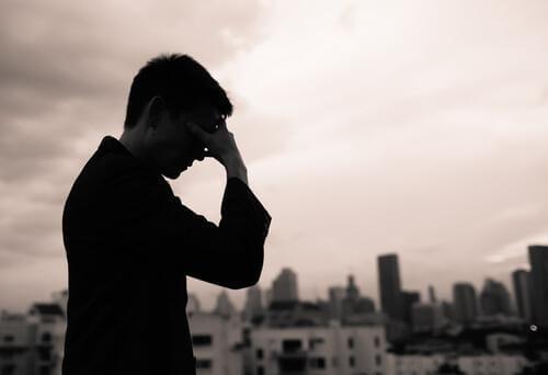 Mann fasst sich traurig an den Kopf.