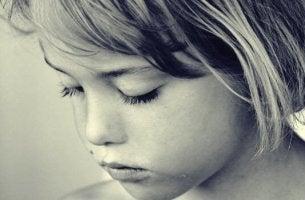 Kind schaut traurig nach unten.