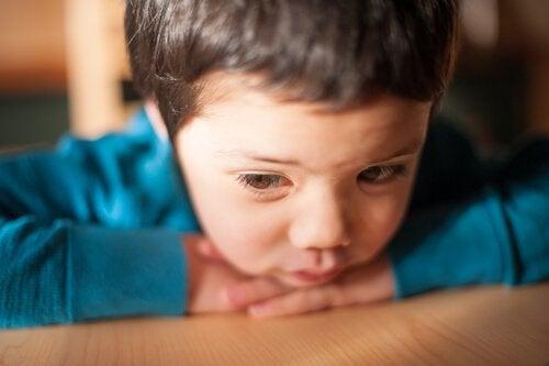 Trauriges Kind stützt sich auf seinen Ellbogen ab