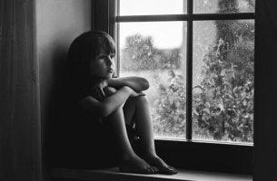 Trauriges Kind sitzt am Fenster.