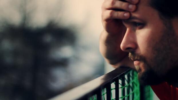 Erschöpfter Mann stützt seinen Kopf auf ein Geländer