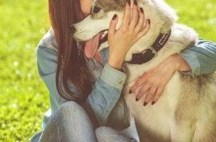 Eine Frau umarmt ihren Hund.