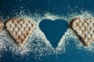 Das Bild zeigt Waffeln mit Puderzucker bestäubt, die in Herzform gebacken sind.
