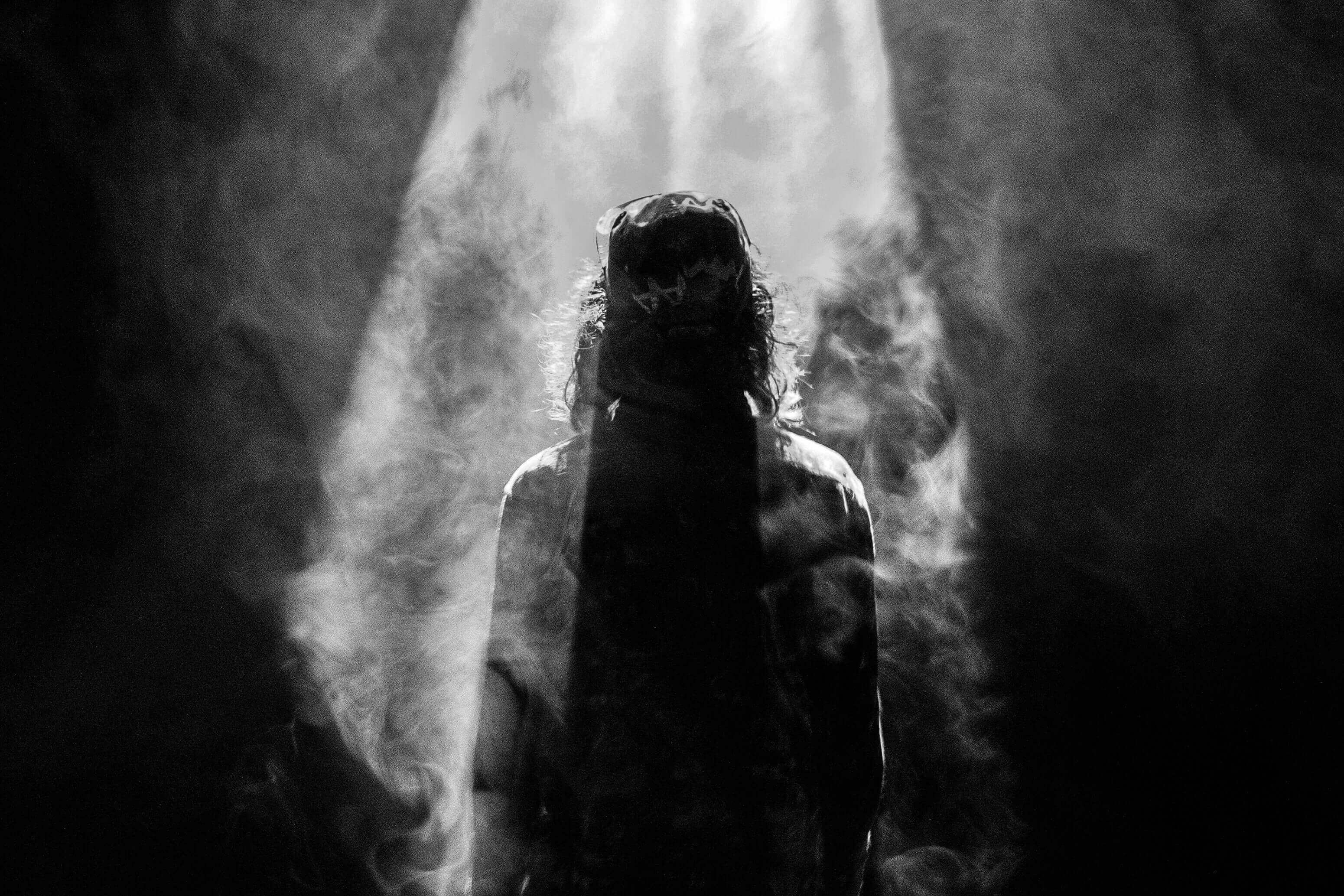 Mann steht mit Rücken im Lichtstrahl und ist umgeben von Dunkelheit