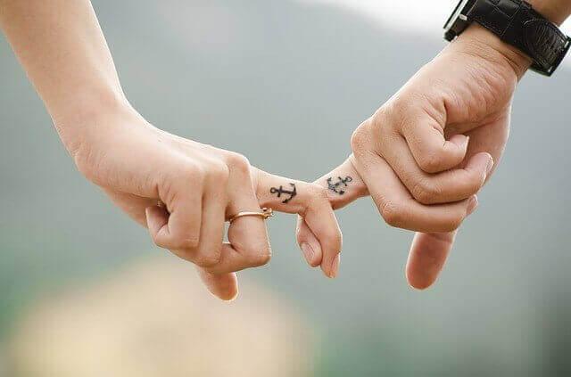 Händchenhalten mit Fingern mit Anker-Partner-Tattoo