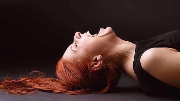 Eine rothaarige Frau kann nicht aufhören zu lachen.