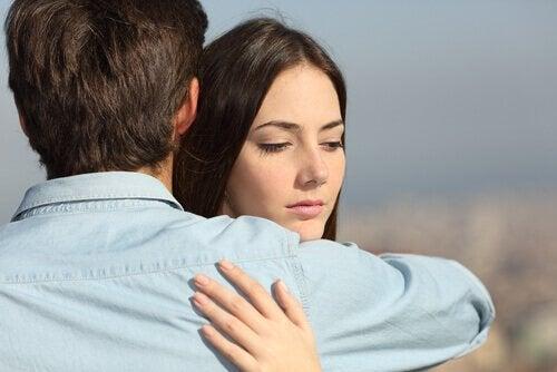 Eine Frau umarmt ihren Partner, blickt dabei aber misstrauisch.