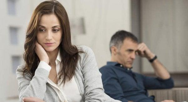 Besorgte Frau schaut nach unten, ihr Partner im Hintergrund