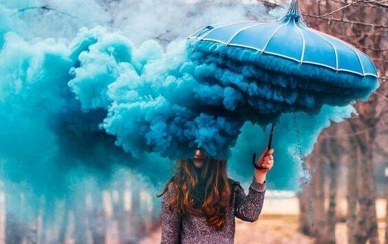 Frau mit blauem Regenschirm und blauem Rauch