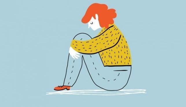Frau sitzt deprimiert auf dem Boden