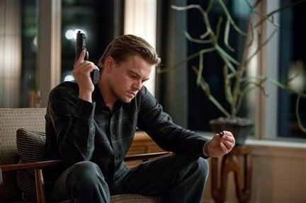 """Dom Cobb, die Hauptfigur aus """"Inception"""", hält eine Waffe in der einen Hand und in der anderen ihr Totem."""