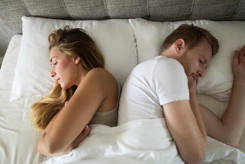 Ein frustriertes Paar liegt Rücken an Rücken im Bett.