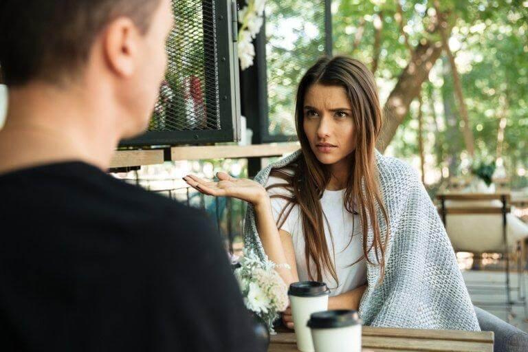Eine Frau argumentiert, ihr Partner sitzt gegenüber und hört zu. Wie kann man Kommunikationsfehler vermeiden?