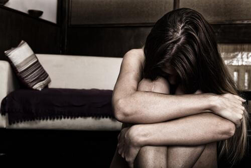 Traurige Frau sitzt zusammengekauert am Boden