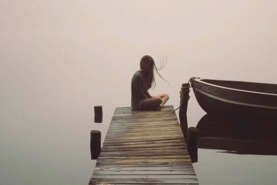 Eine Frau sitzt nachdenklich am Ende eines Stegs