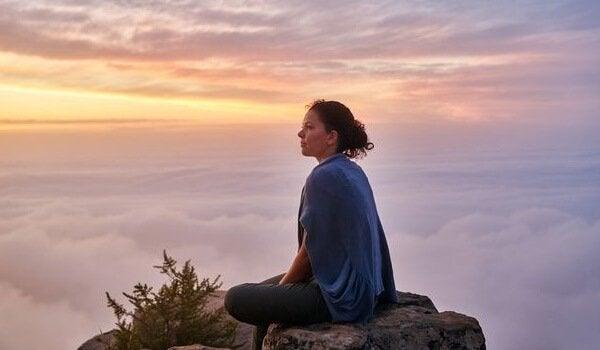 Frau, die auf einem Stein sitzt