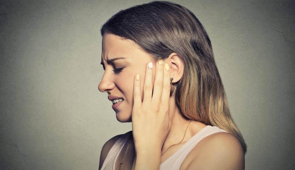Eine Frau, die unter Misophonie leidet, fasst sich ans Ohr.