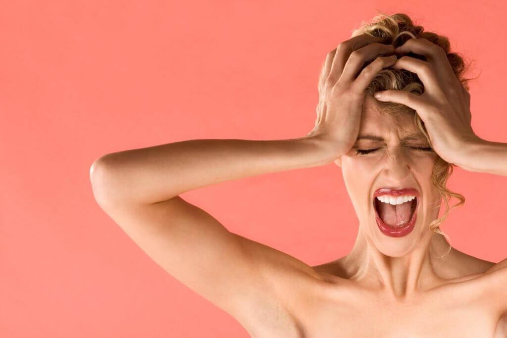 Eine Frau hält sich zum Schutz die Ohren zu.