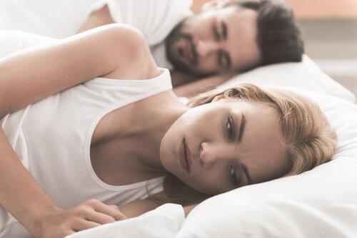 Frau liegt neben ihrem Partner im Bett und denkt nach.