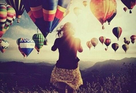 Frau umgeben von vielen Heißluftballons