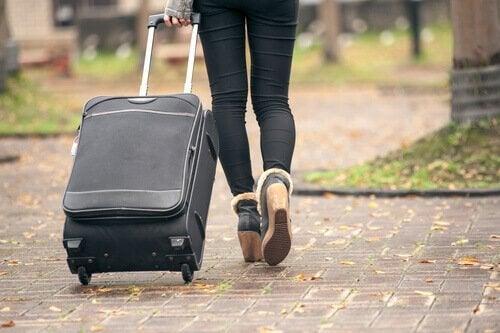 Eine Frau zieht einen Koffer über den Bürgersteig.